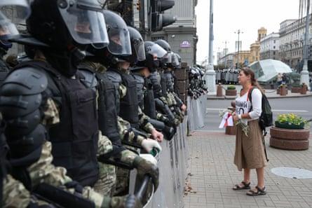 Une femme tient des fleurs et un drapeau blanc-rouge-blanc alors qu'elle se tient devant les forces de l'ordre à Minsk dimanche.