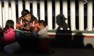 A migrant and his children wait to hear if their number is called to apply for asylum in the US in Tijuana on 25 January.