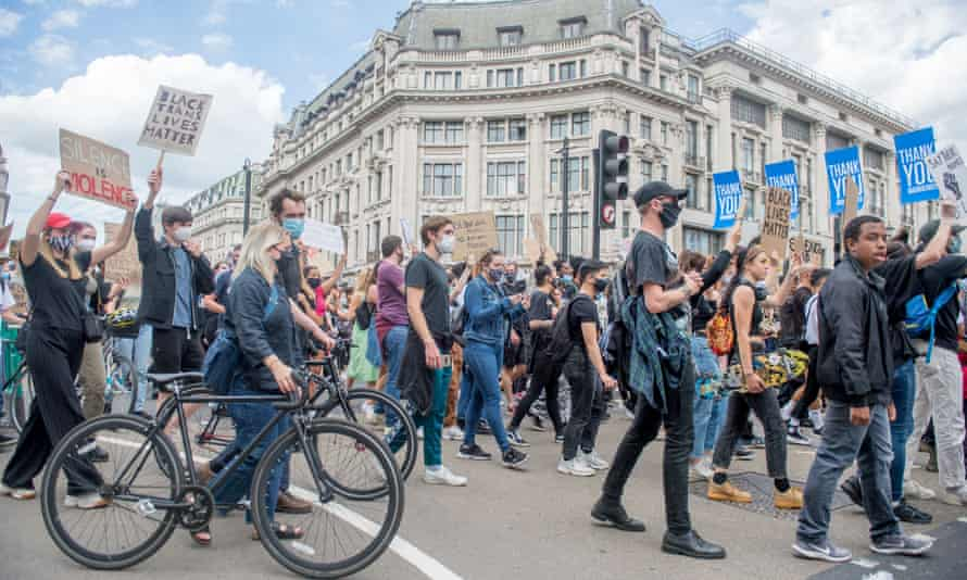 Supporters of the Black Lives Matter movement carry banners and march along Oxford Street, London, on 21 June.