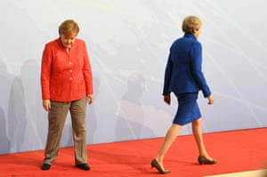 The British PM, Theresa May, leaves the stage after being officially welcomed by Merkel