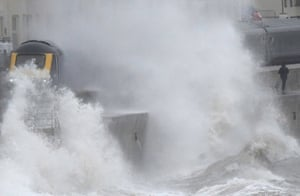 Large waves hit the sea wall with Storm Brendan bringing high winds and heavy rain, as a train passes through Dawlish, southwest Britain