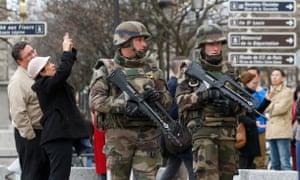 在澳门娱乐官方网址事件发生后,游客们在巴黎圣母院大教堂附近停下来拍照作为法国军事巡逻队。