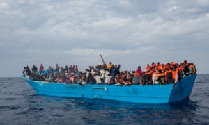 Refugees and migrants put on life jackets distributed by rescue crews off Lampedusa last week.