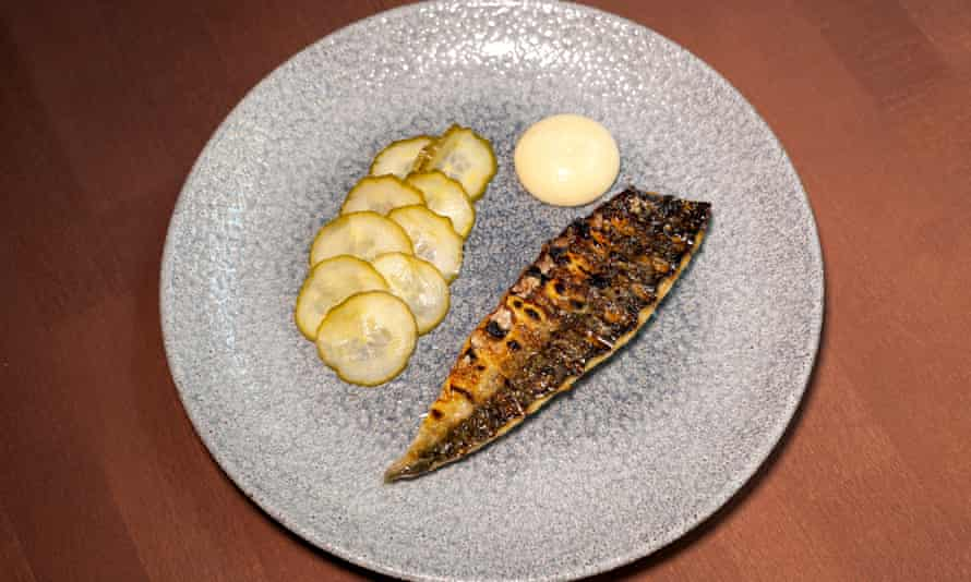 A cooked mackerel with slices of pickled cucumber to the side on a round pale blue plate