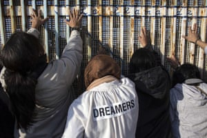 People gather on the Mexican side of the border fence to touch hands during the celebration of the Posada Sin Fronteras or Posada Without Borders at the Mexican-US border on December 16, 2017, as part of the Christmas celebrations in Playas de Tijuana, northwestern Mexico. The Posadas is a Catholic ritual that reenacts Mary and Joseph's journey from Nazareth to Bethlehem in search of a birth place for the Christ Child.