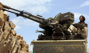 A member of pro-government forces in Yemen sits on a heavily armoured vehicle in Sana'a.