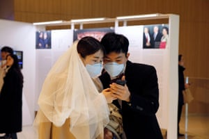 Bride and groom in face masks looking at phone