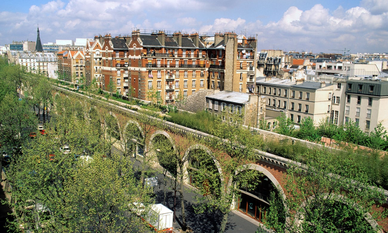 The image shows the  Promenade Plantée, an park built on an abandoned viaduct. The stricture resembles an elevated train track, made of brick arches, with shop fronts in the space under the arches. The top of the viaduct has grasses, shrubs, and benches, with trees on either side of it, and the buildings of Paris in the background