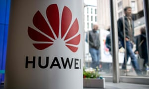 Huawei sign on pillar with pedestrians in background