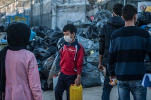 A boy wears a surgical mask to protect from coronavirus at the Moria refugee camp near Mytilene on the Island of Lesvos last week
