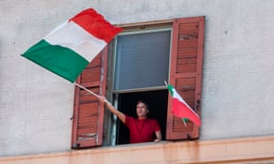 A resident waves the Italian flags in the Garbatella district of Rome on April 25, 2020