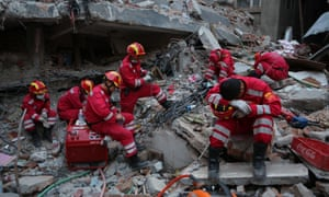 Members of China's international search and rescue team take a rest amid the ruins of a site in Kathmandu