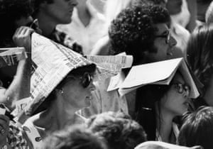 Spectators at Wimbledon Tennis Championships protect themselves from the sun wearing newspaper hats and books on their heads