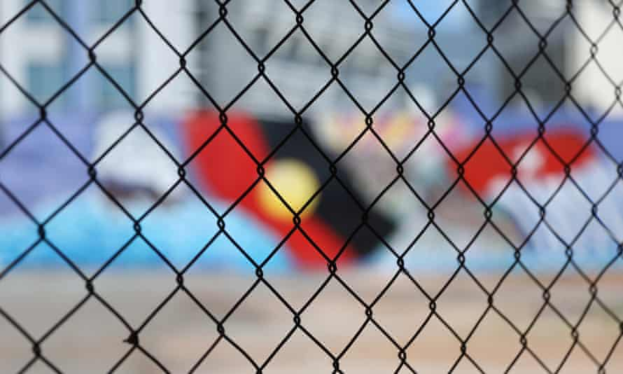 A wire fence in front of an Indigenous flag mural in Darwin