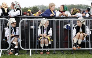 Girls dressed in traditional attire chat wait for a beatification mass held by Pope Francis in Blaj, Romania