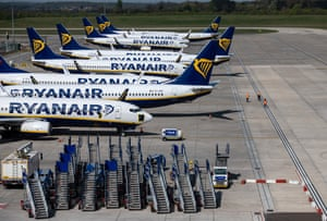 Three people walk on the runway among parked and temporarily out of service Ryanair passenger aircraft at Stansted airport outside London.