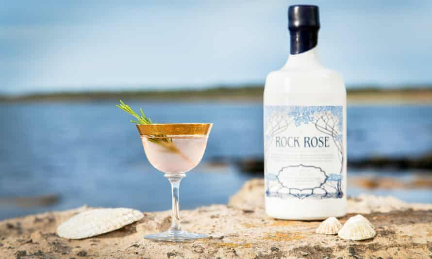 Bottle of Rock Rose gin and a glass of it perched on rocks on the north coast of Scotland. PR image for Dunnet Bay distillery, Scotland.