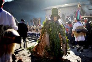 A reveller dresses in a leaf costume during carnival celebrations in Ituren, northern Spain