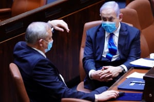 The Israeli prime minister, Benjamin Netanyahu, right, and Benny Gantz, Netanyahu's partner in his new unity government, wear masks during a swearing-in ceremony at the Knesset in Jerusalem