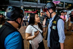 A police officer argues with a women after clashes with anti-government protesters in the Kwai Fong district of Hong Kong.