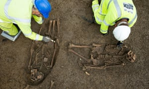 A set of Roman burials being carefully excavated by archaeologists