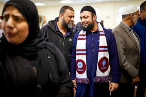 Imam Shift Ur Rehman, wearing a West Ham United scarf, talks with worshippers at Liverpool Mosque and Islamic Institute.