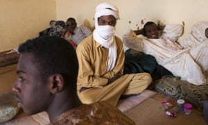 Migrant smugglers relax in a living room in Agadez.