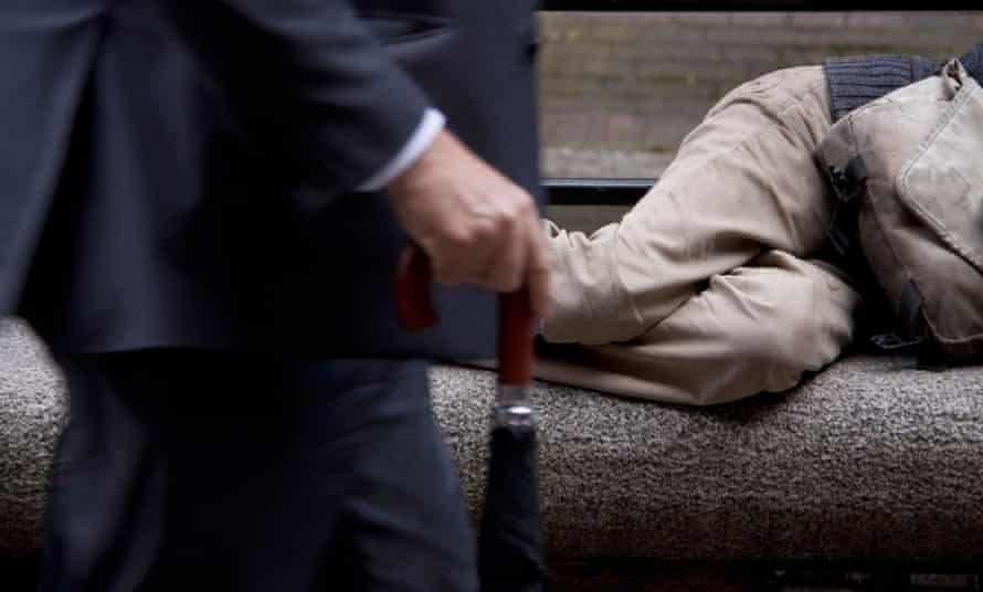 A businessman walking by a homeless person