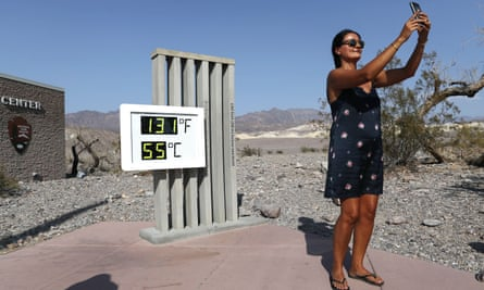 A visitor takes a selfie in front of the unofficial thermometer at Furnace Creek visitor center.