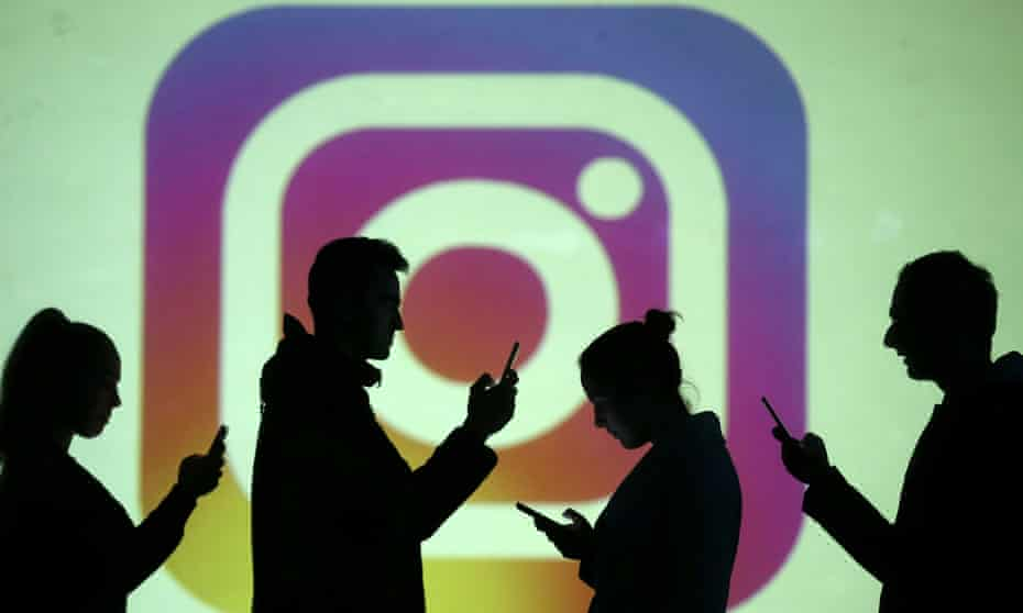 Silhouettes of mobile users are seen next to a screen projection of the Instagram logo