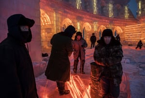 Workers gather lights that will illuminate the ice sculptures