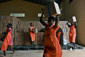 Workers carry cartons of supplementary food rations to repackage into reinforced containers at a warehouse in Juba to be transferred onto a World Food Programme (WFP) cargo plane to be dropped close to a village in Ayod county, South Sudan