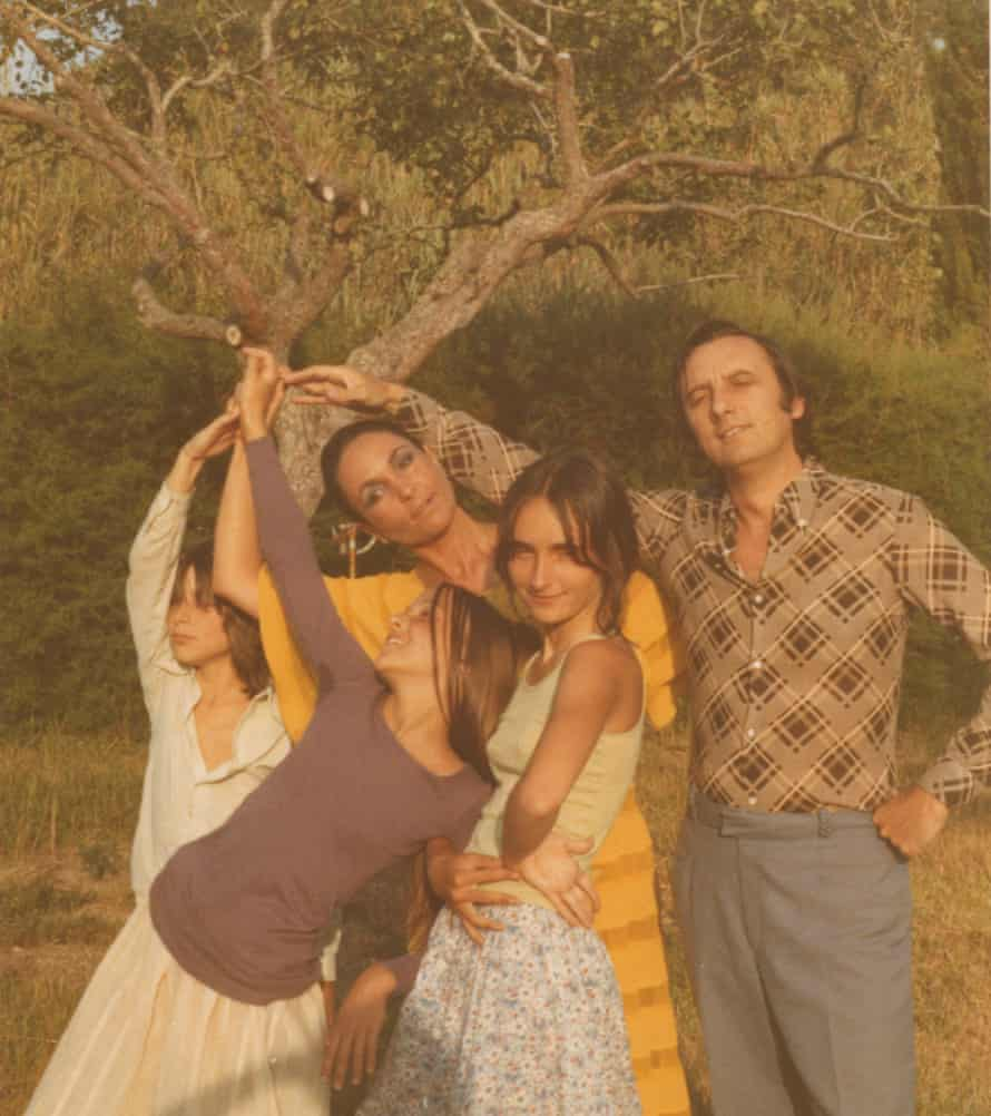 A shot from the 1960s with Rego, her son Nick Willing, two daughters, and late husband, Victor, standing together, each with a hand raised and touching, near a tree