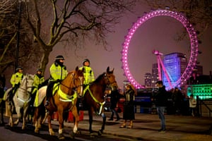 Mounted police officers patrol the Victoria Embankment opposite the London Eye