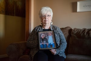 """Cindy Anderson poses with a photo of her late husband """"Butch"""" in her home on December 23 in Kennett, Missouri. The city has been without a hospital since the closing of Twin Rivers Regional Medical Center in 2018. Photograph: Brandon Dill for The Guardian"""