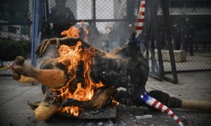 An 'Alebrije', a traditional Mexican figure, with the face of Donald Trump burns in front of the US embassy building in Mexico City during a protest.