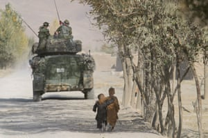 Kabul, 2003. Afghan boys walk along a path while International Security Assistance Force troops on their armoured vehicle guard the perimeter of a school in Shakadara province.