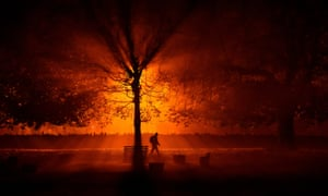 A man uses a torch to walk through a park during cold fog at night in Athboy, Ireland, 31 October.
