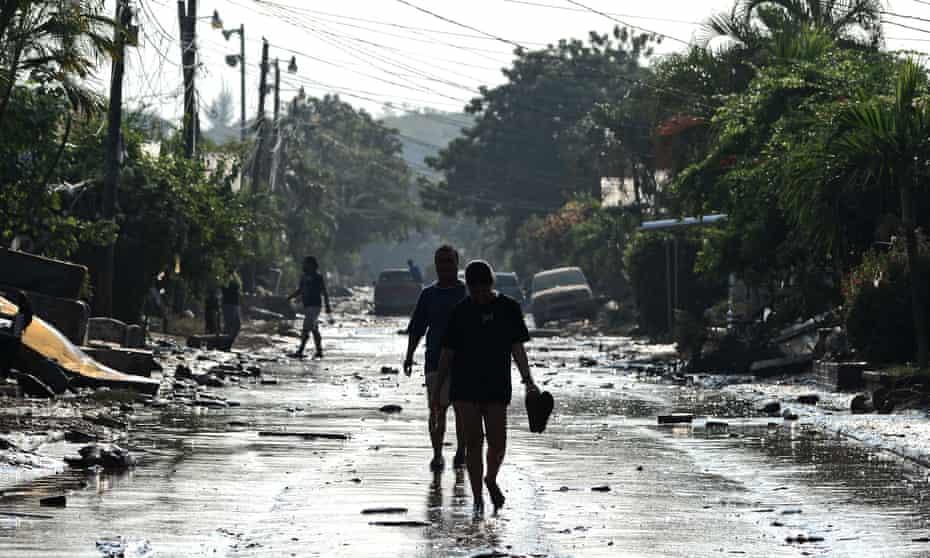 People walk along a street in Planeta, municipality of La Lima, one of the hardest hit communities.