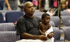 Will Sutton, an evacuee, holds his 11-month son Jayden at the Lakewood Church in Houston.
