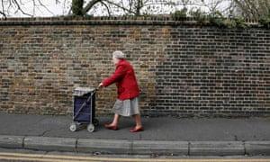 An elderly woman pushes a shopping trolley