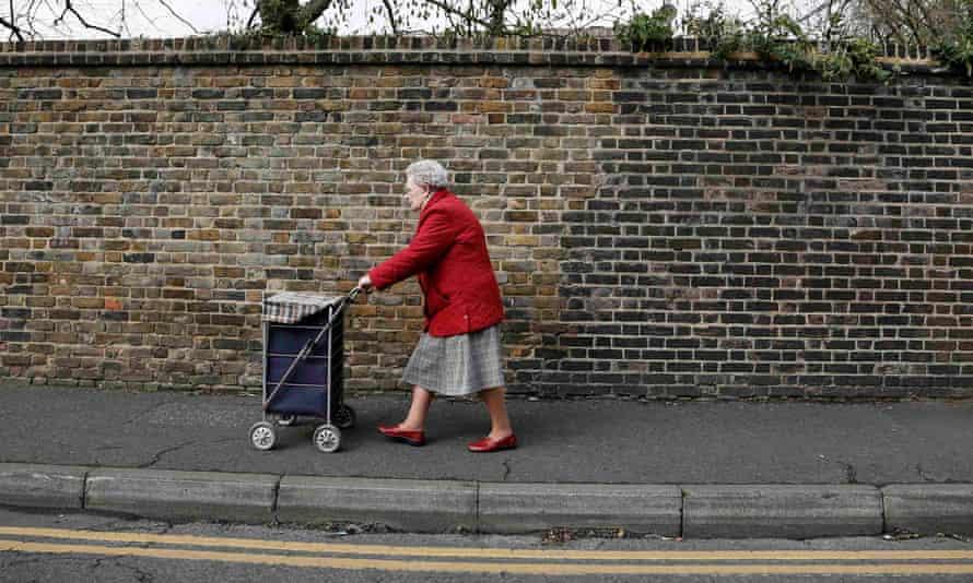 Elderly woman pushes trolley down street
