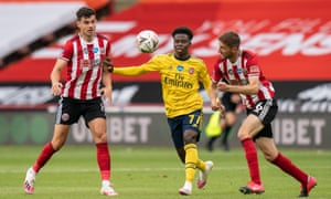 Arsenal's Bukayo Saka (centre) tries to get the better of two Sheffield United players.