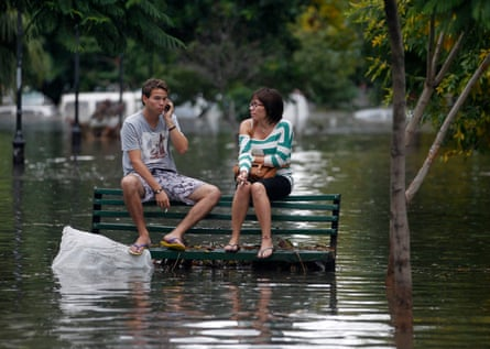 Residents sit on a bench at a flooded public square after a rainstorm in Buenos Aires in 2013.