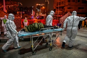 Medics arrive with a patient at Wuhan Red Cross hospital, 25 January