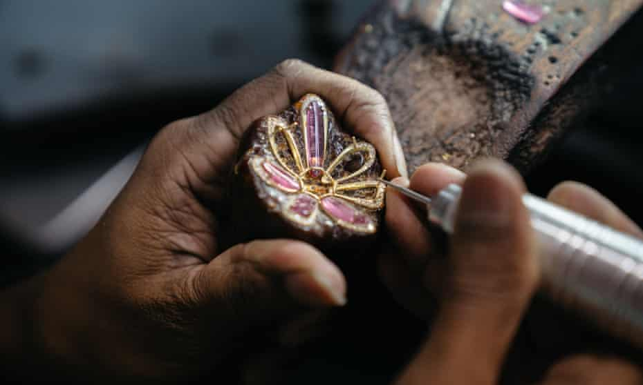 Adding gems to an earing design in a Jaipur workshop.