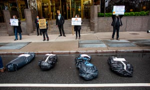 Protestors take part in a nationwide protest against Donald Trump as they place fake body bags on the street in front of the Trump International Hotel on 18 April in New York City.