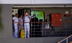 Crew members aboard a luxury cruise ship docked in Rio de Janeiro, Brazil, wear protective masks and gloves.
