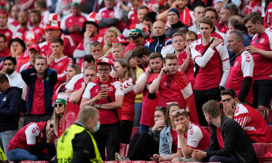 Denmark fans look on in horror as Christian Eriksen is treated after collapsing on the pitch at Parken in Copenhagen on Saturday.