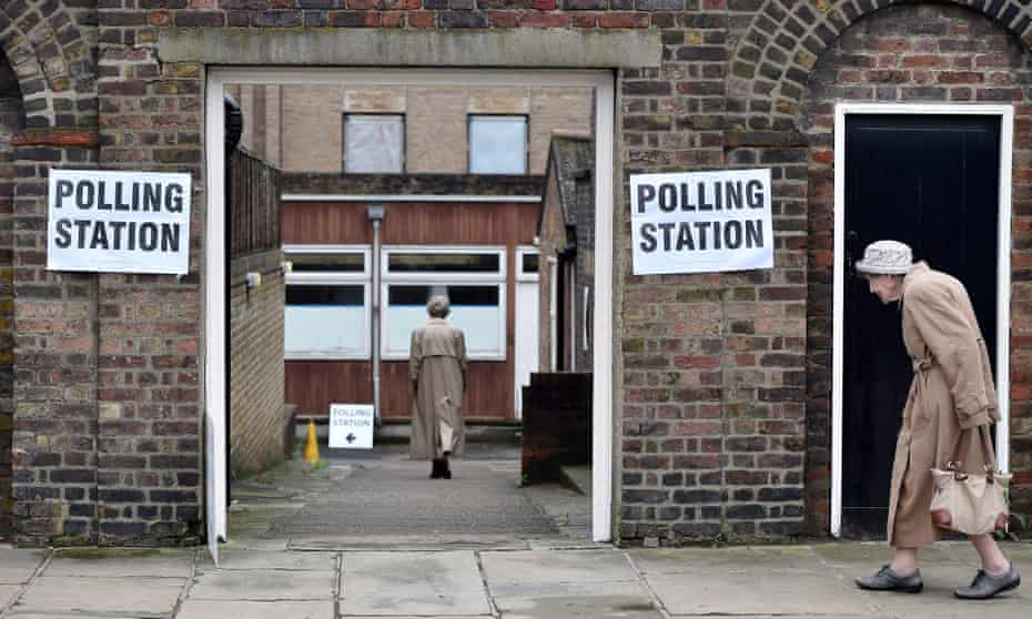 Two women enter a polling station to vote in the EU referendum in London.